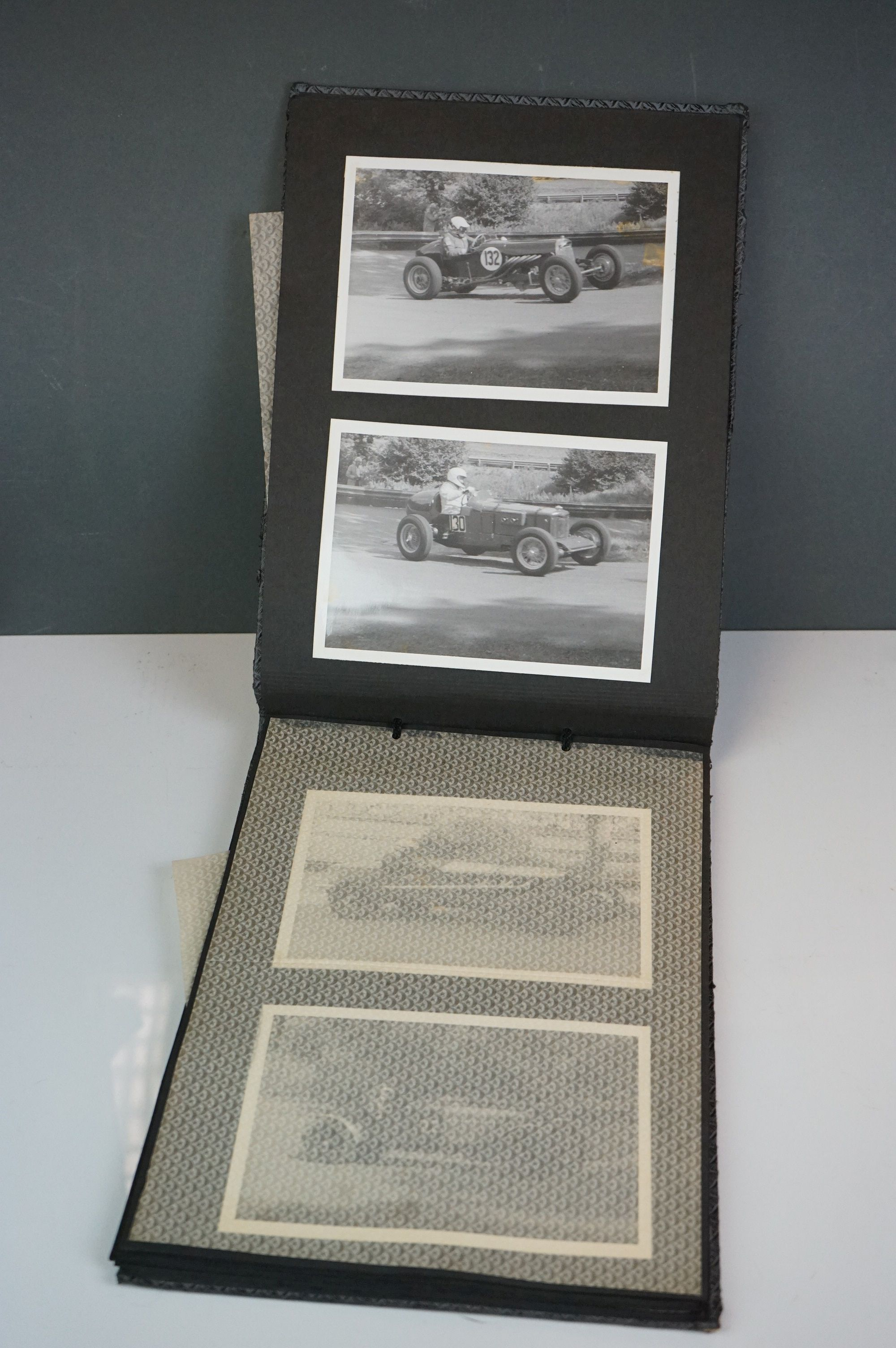 A vintage photograph album with vintage black and white photos of motor racing cars.