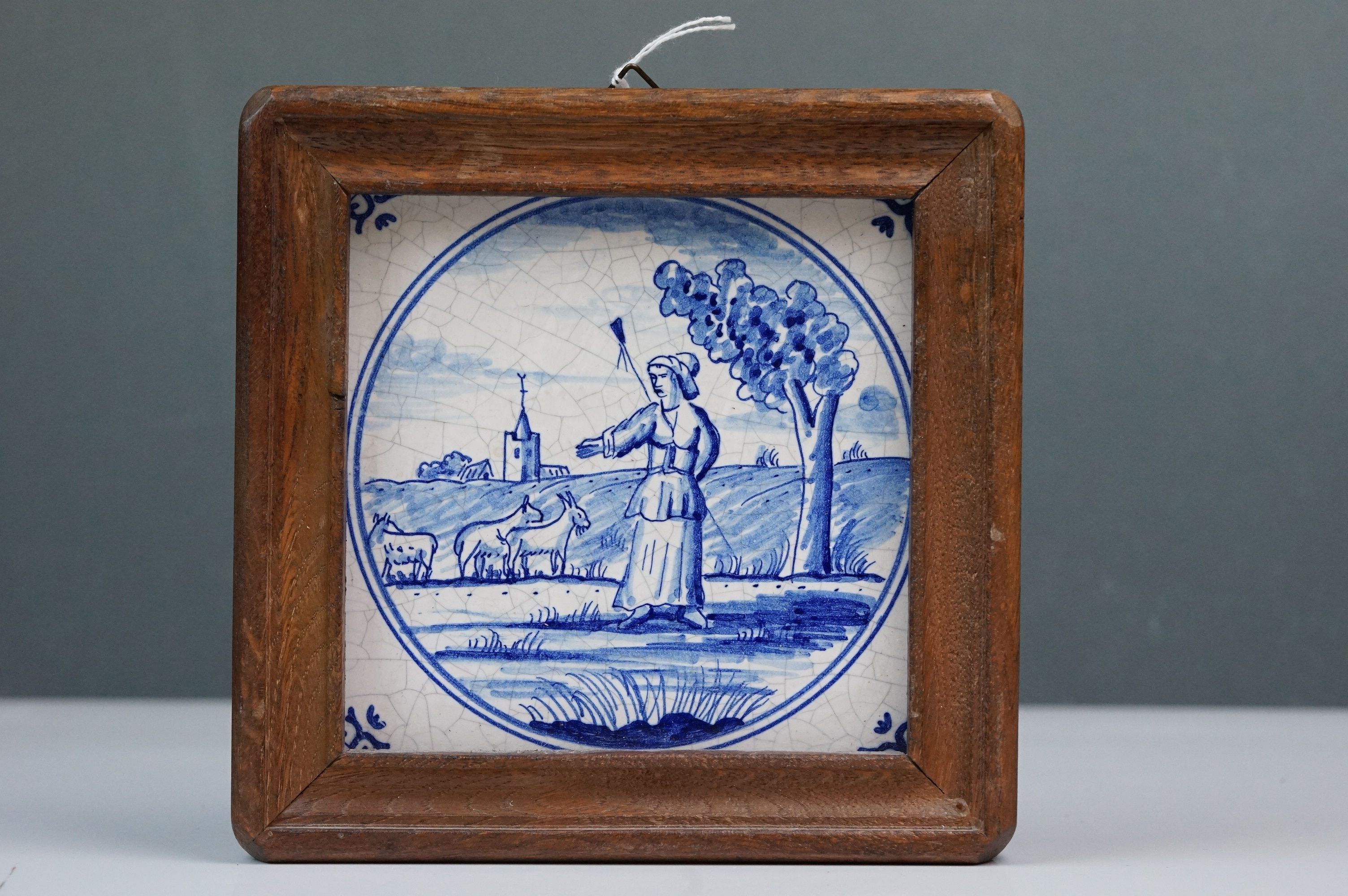 Dutch Delft-style blue and white tile depicting a shepherdess with goats, impressed dove mark to