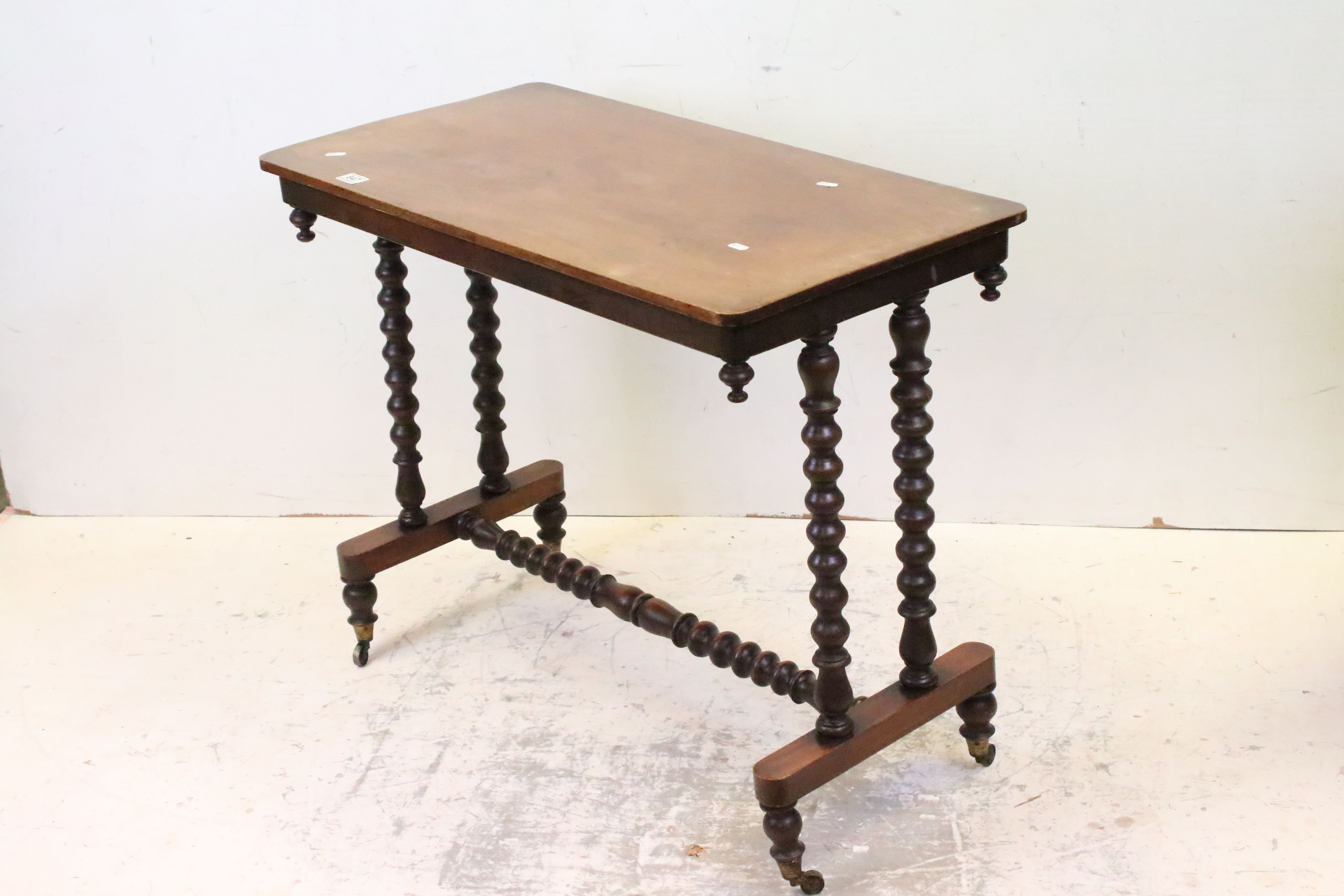 Victorian Mahogany Side Table raised on bobbin supports and cross-stretcher, raised on castors,