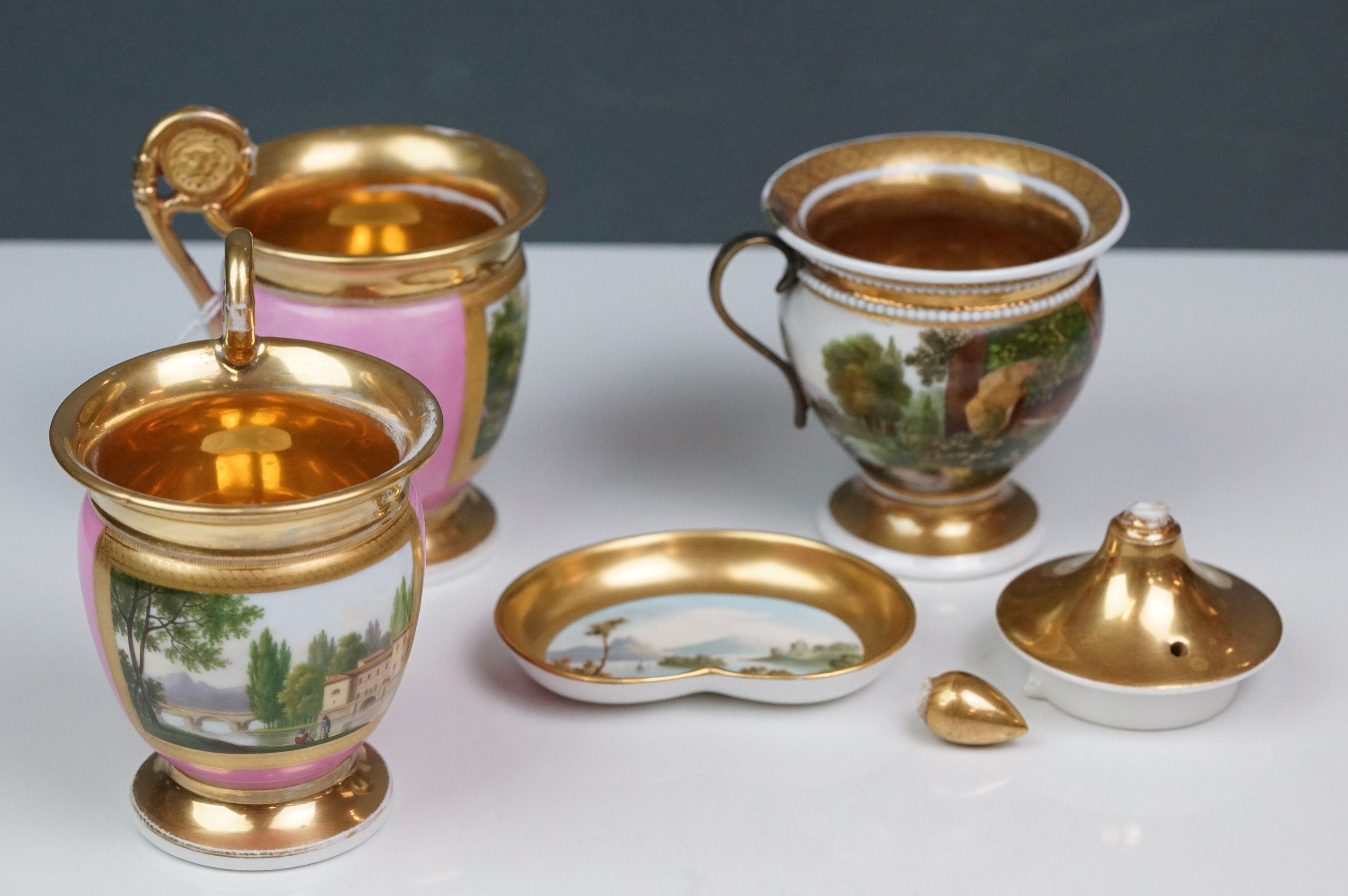 Pair of hand painted Dresden cups, each depicting a different scene: castle and lake scene with