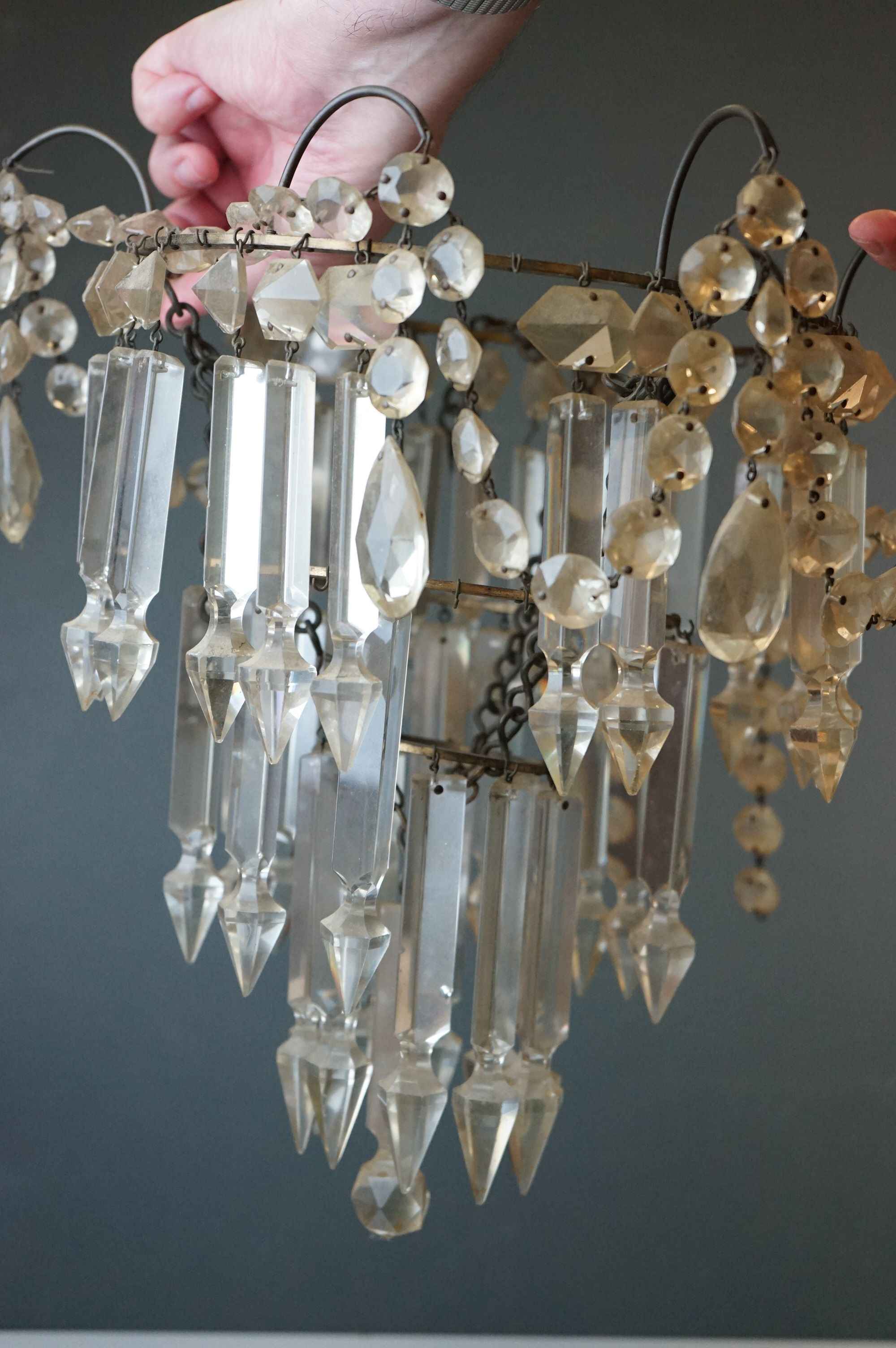 A antique three tier chandelier with glass droplets.