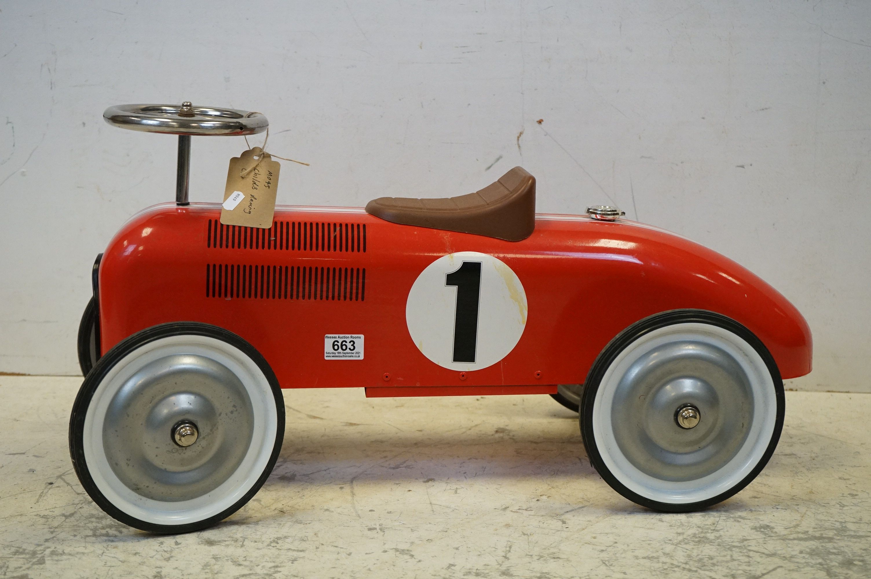 A contemporary metal red Childs racing car.