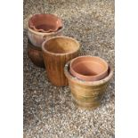 A group of eight terracotta plant pots / planters.