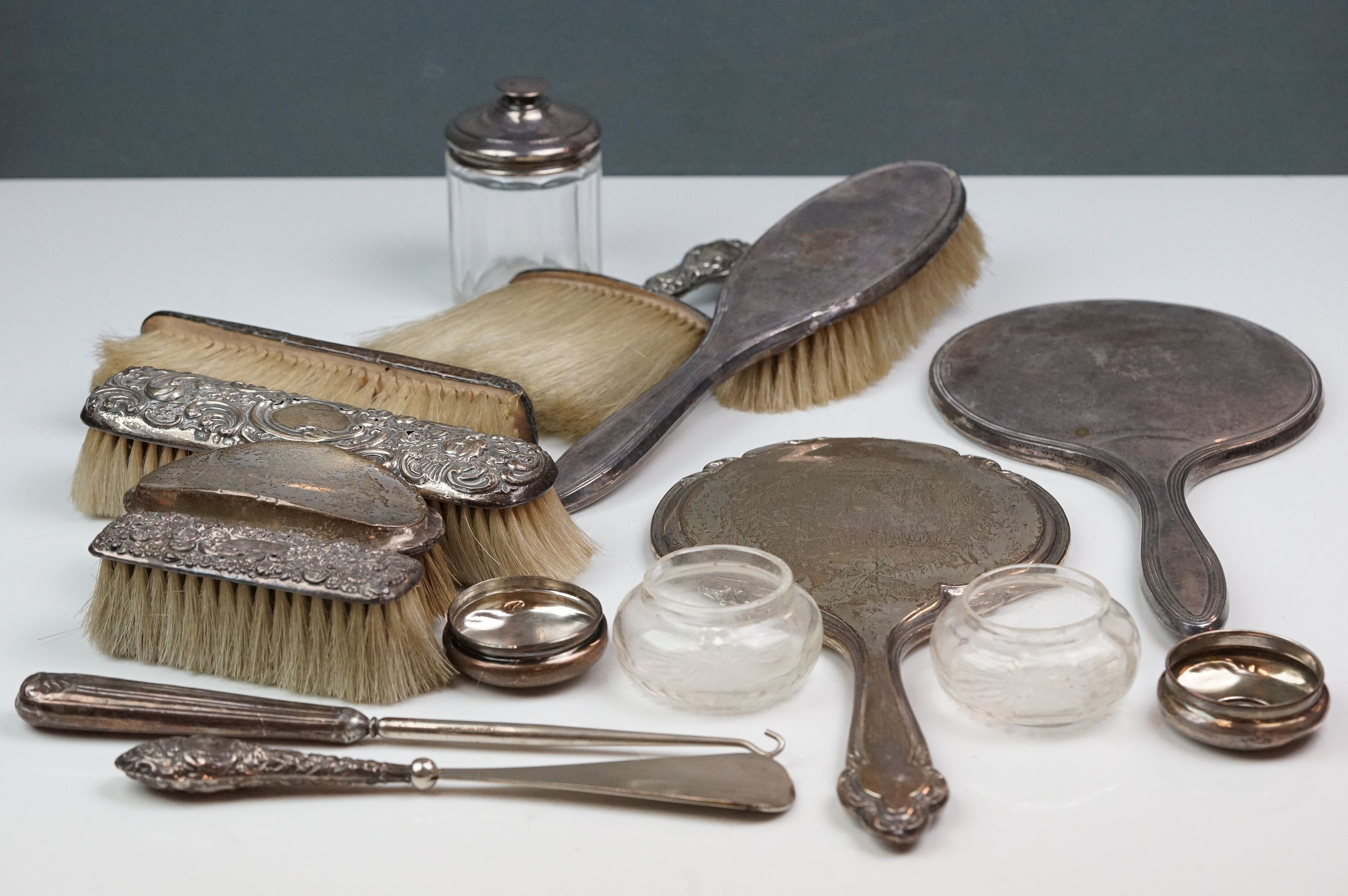 Silver topped dressing table items to include hand mirrors, brushes, jars, button hook and shoe