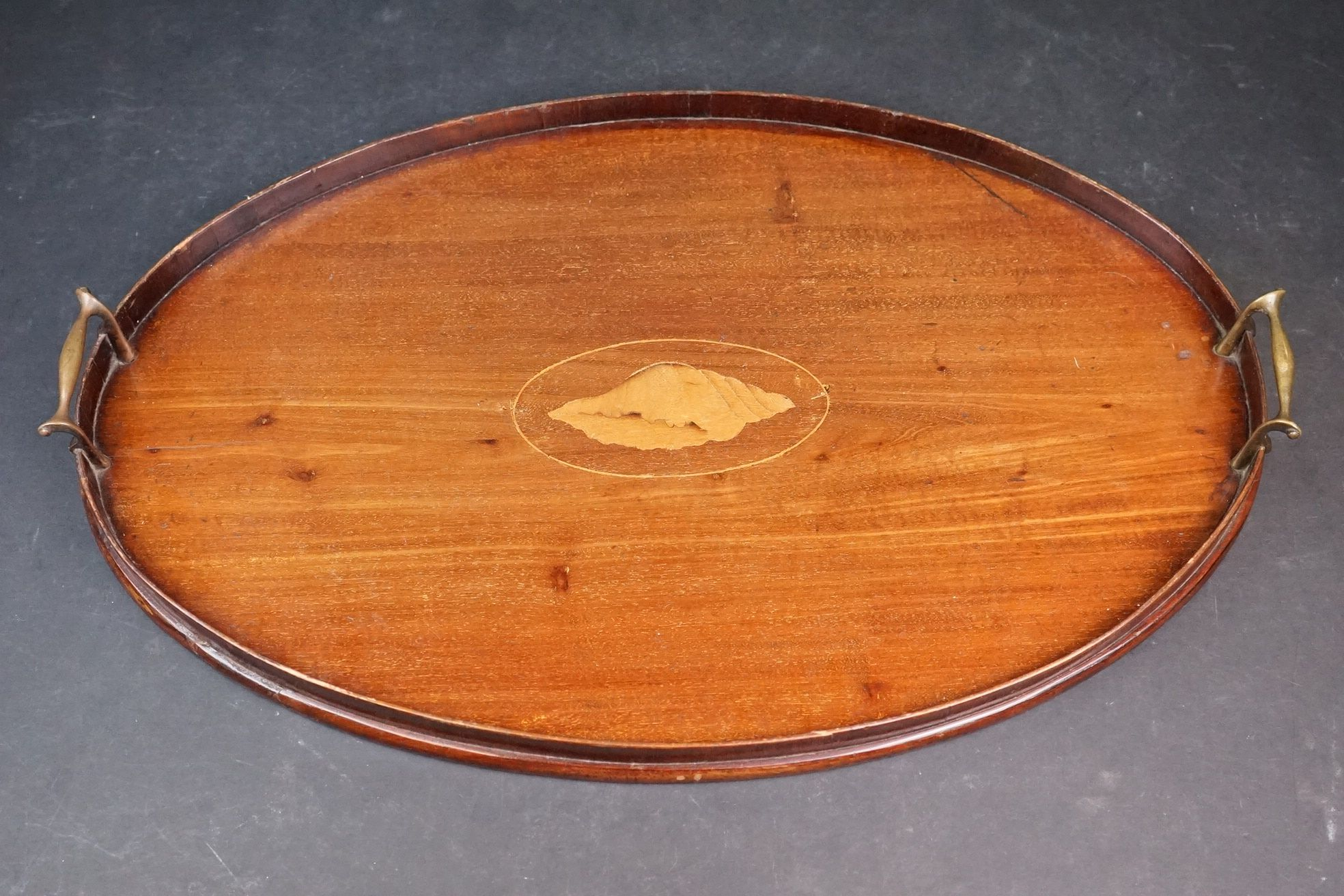 An early 20th century wooden oval serving tray with inlayed decoration.