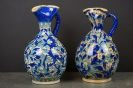 Pair of Persian Glazed Jugs with pinched spouts decorated with foliage in shades of blue, 25cms high