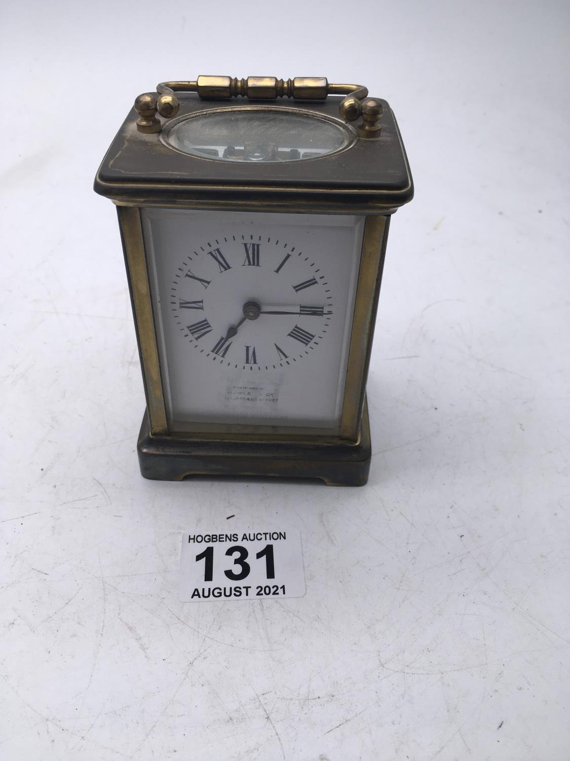 Maple & Co a brass bound carriage clock with enamel dial, movement runs for 1 minute approx