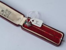 A boxed art deco gold & platinum stick pin set with ruby's, emeralds & diamonds