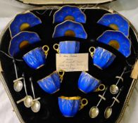 A boxed Coal port coffee set in blue and gilt with silver and enamelled spoons