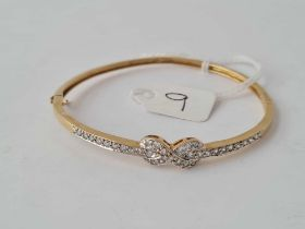 An attractive hinged bangle set with CZ ribbon bow in 9ct - 8.4 gms inc