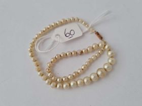 A small childs pearl necklace with gold barrel clasp