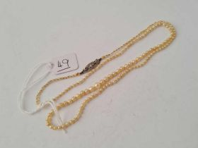 AN EDWARDIAN NATURAL SEED PEARL NECKLACE WITH 18CT GOLD DIAMOND CLASP
