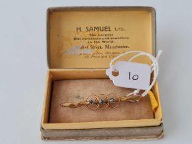 A pretty bar brooch with three blue stones 9ct gold