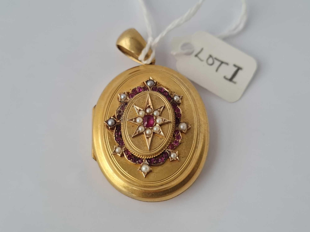A attractive Victorian oval locket front with ruby's and pearls hinge centre with two photo