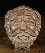 "A 19th Century Carved Oak Appliqué in the form of a bearded face mask, 6"" x 5"" (15 cm x 12.5 cm)."