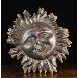 An 18th Century Double-sided Carved Wooden Sunburst Facemask; probably a pub sign,