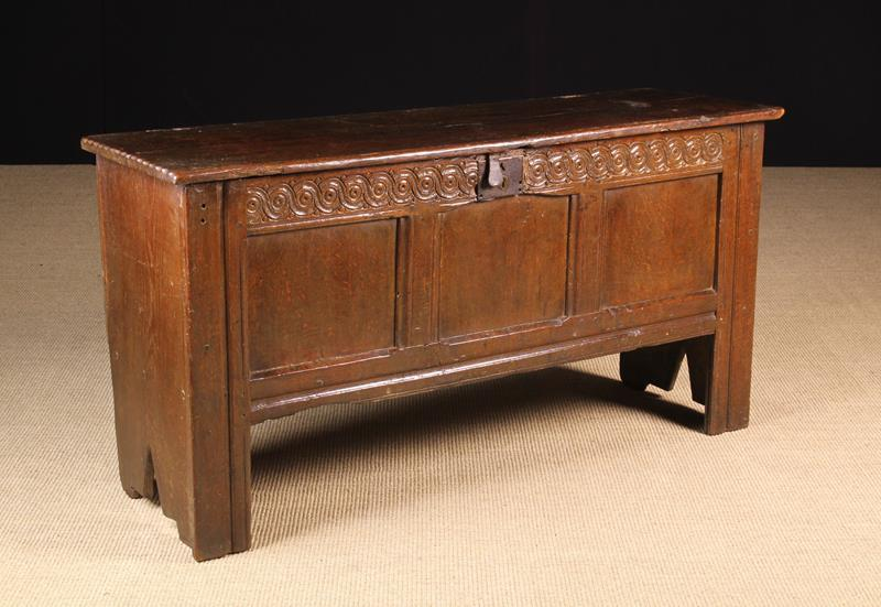 A 17th Century Joined Oak Coffer. The plank lid with chip carved ends and a moulded front edge.