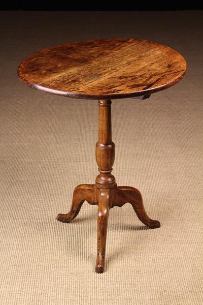 "A Late Georgian Oak Tilt-top Tripod Table, 24¼"" (66.5 cm) high, 22"" (56 cm) in diameter."