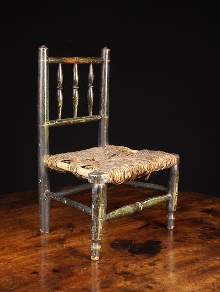 A 19th Century Miniature Dales Chair having a spindle back and rush seat with painted decoration