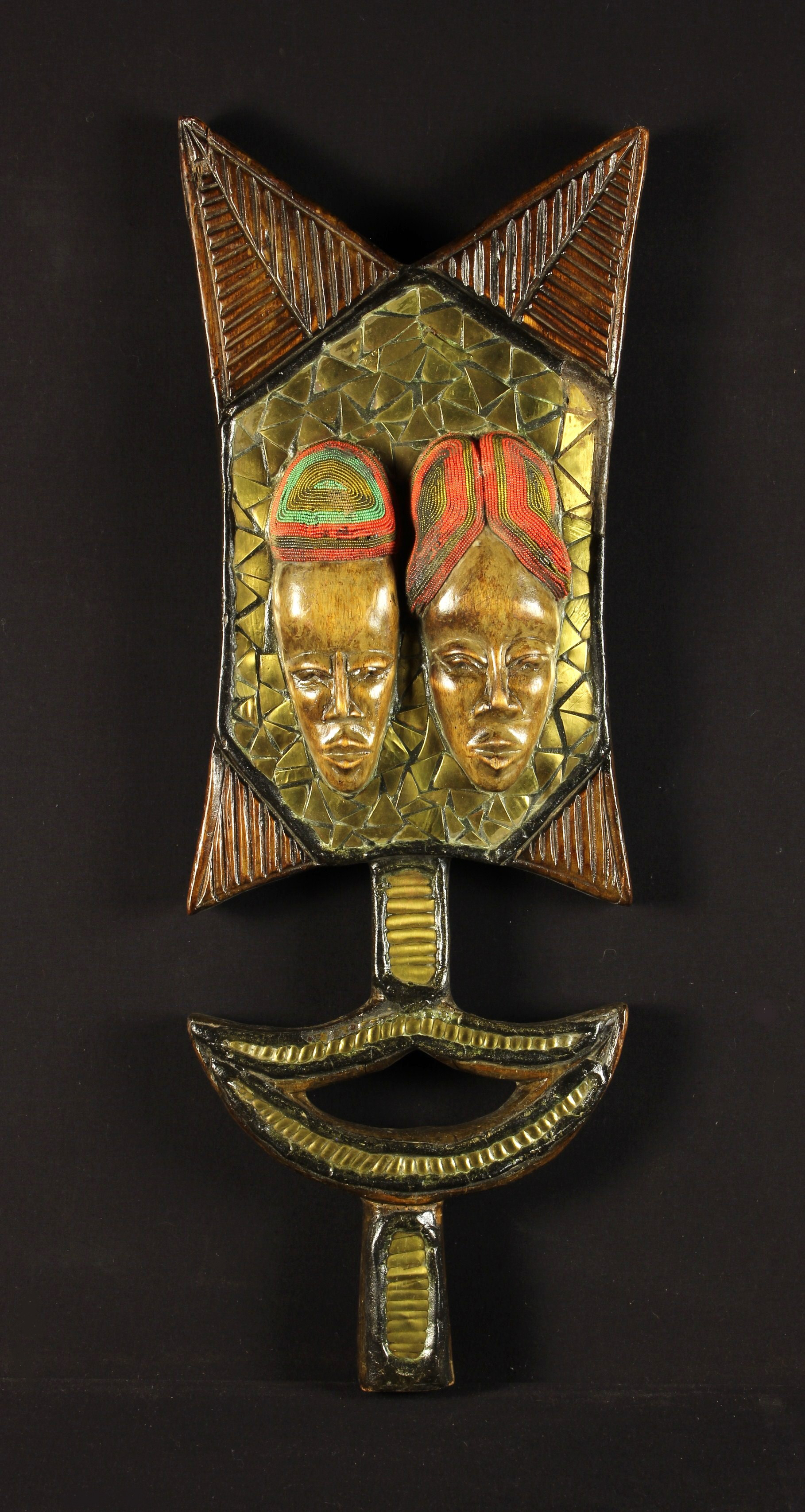 A Carved African Decorative Shaped and Pierced Wooden Slab emblazoned with a pair of relief carved