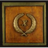 A 19th Century Painted Panel appliquéd with a carved wooden XP monogram within a laurel wreath to