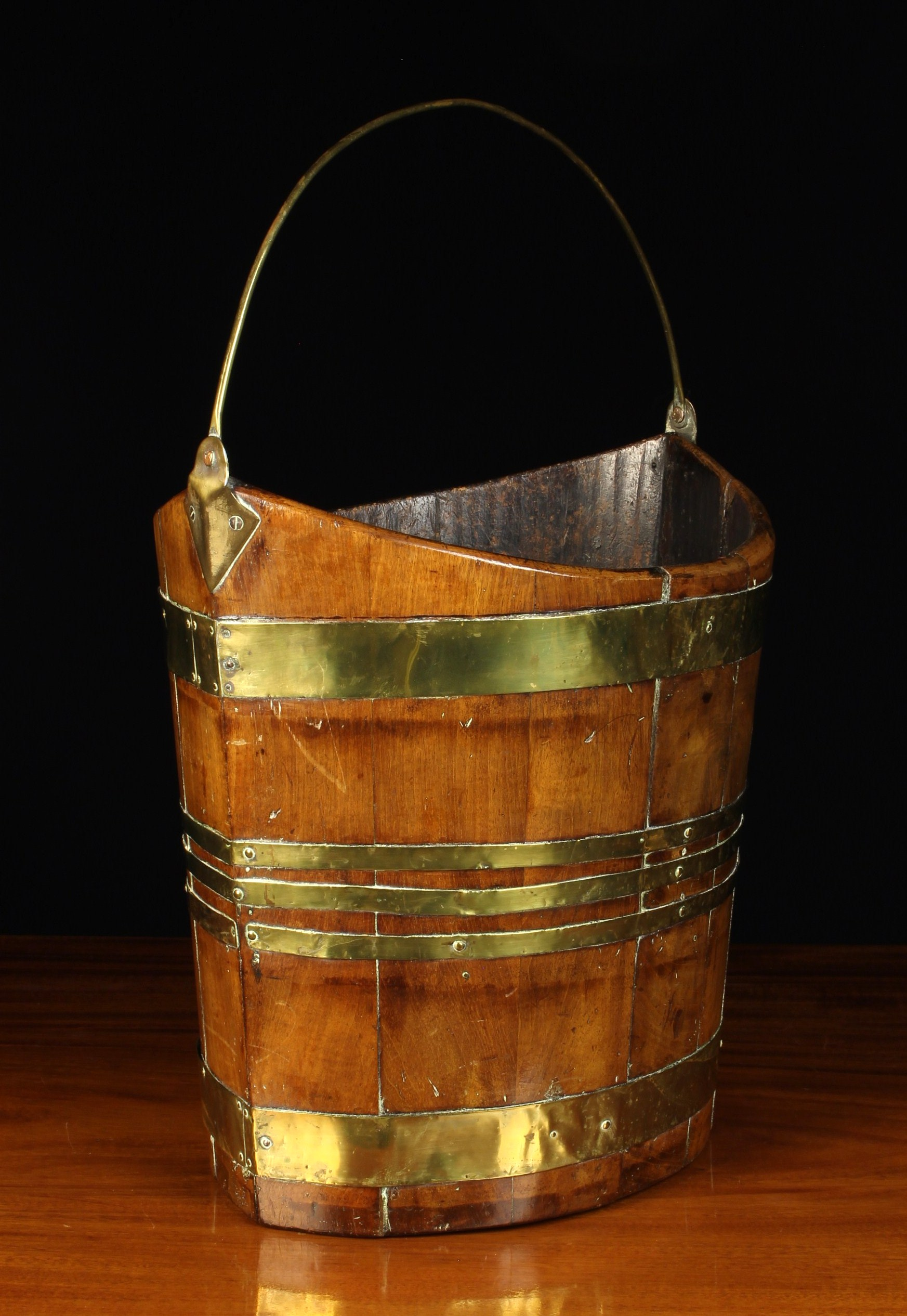 An Early 19th Century Navette Form Peat Bucket with brass bound mahogany staves and a brass swing