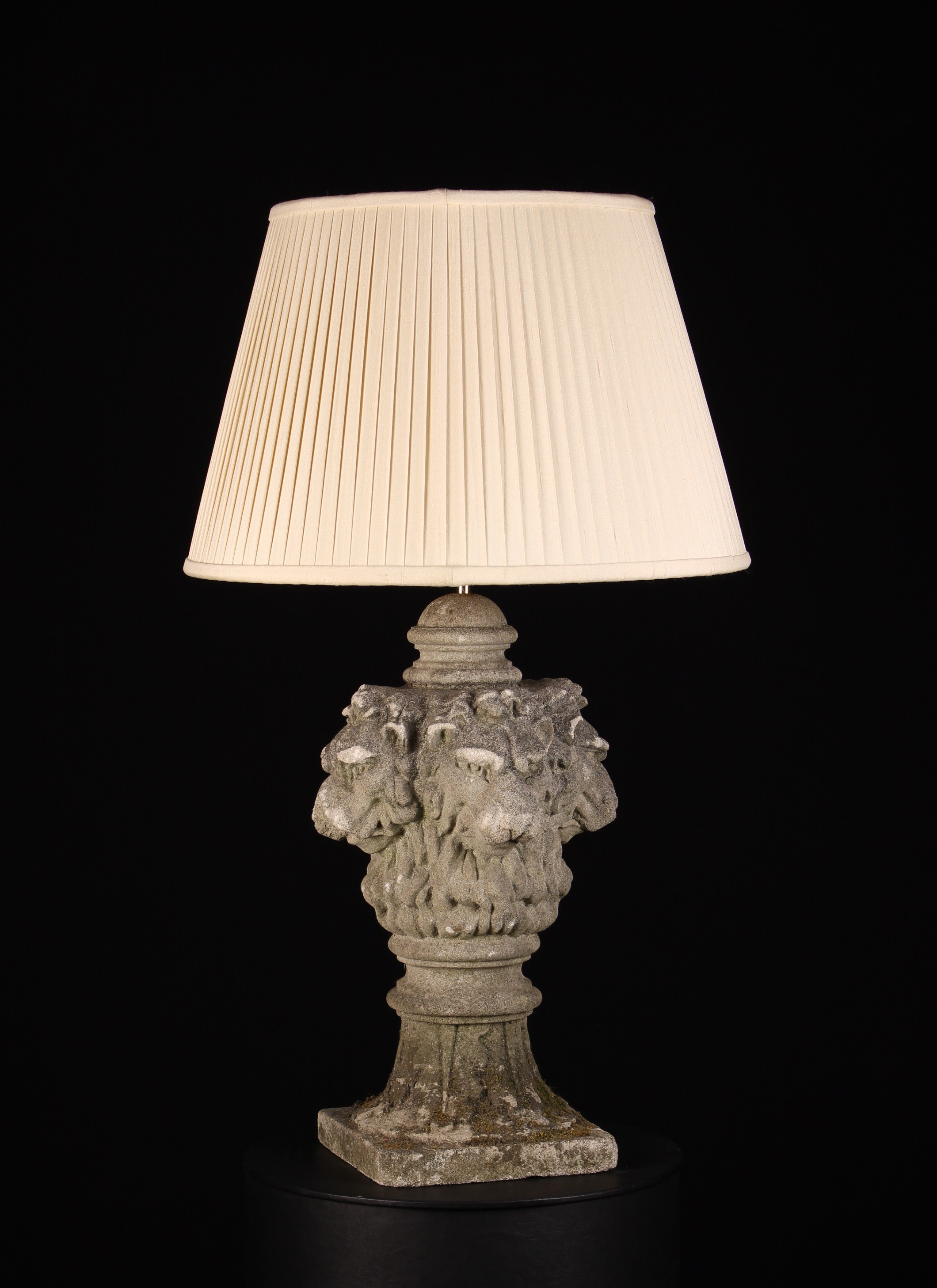 A Handsome Table Lamp incorporating an architectural stone pediment carved with four lion heads;