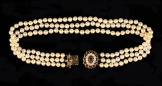 A Three Strand Pearl Choker with a 9 carat gold clasp set with simulated garnets & small pearls.