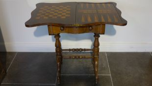 A Victorian rosewood foldover top games worktable with games board top over a fitted drawer on