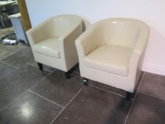 A pair of faux leather cream tub chairs, some usage marks but generally good