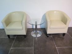 A pair of faux leather cream tub chairs with a glass top coffee table, 49cm x 50cm, some usage marks
