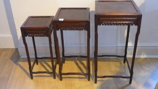 A set of three graduating chinese hardwood side tables with a carved frieze, tallest 62cm x 33cm