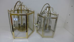 A brass hexagonal hall lantern, 37cm x 25cm, and a similar smaller silvered lantern