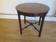 An Edwardian mahogany circular window table with a blind fretwork frieze and fretwork stretchers -