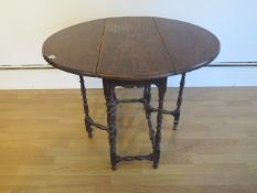 A small oak gateleg table on finely turned supports - Height 66cm x 84cm x 72cm