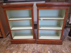 A pair of walnut open bookcases with painted interior and adjustable shelves made by a local