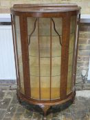 A bowfronted oak 1950's cabinet - Height 122cm x 74cm x 33cm with three glass shelves