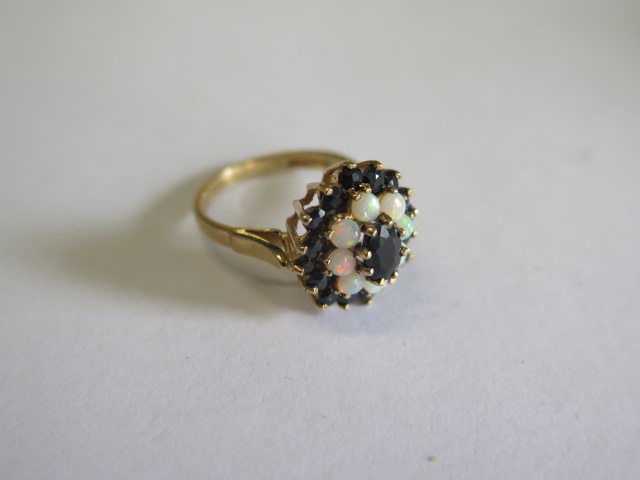 A hallmarked 9ct yellow gold opal and sapphire cluster ring, head 15mm wide, ring size O, approx 3.7