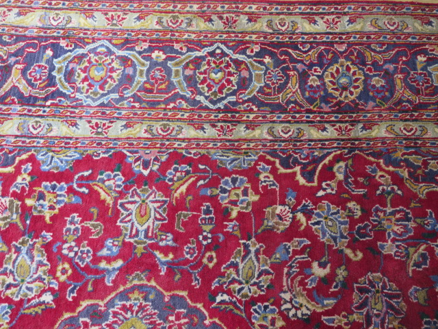 A rich red ground hand woven woollen full pile Persian Kashan carpet with traditional floral - Image 7 of 8