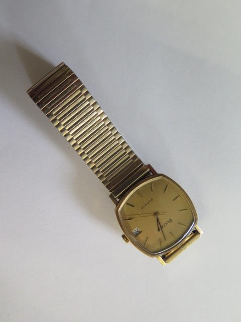 A hallmarked 9ct yellow gold Bulova quartz date wristwatch, 30mm wide on a plated strap, in