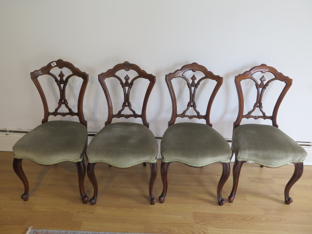 A set of four Victorian walnut side chairs with upholstered seats on cabriole shaped front legs, all
