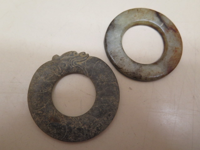 Two jade discs, one with carved dragon on serpent head, 5.2cm and 5.5cm diameter