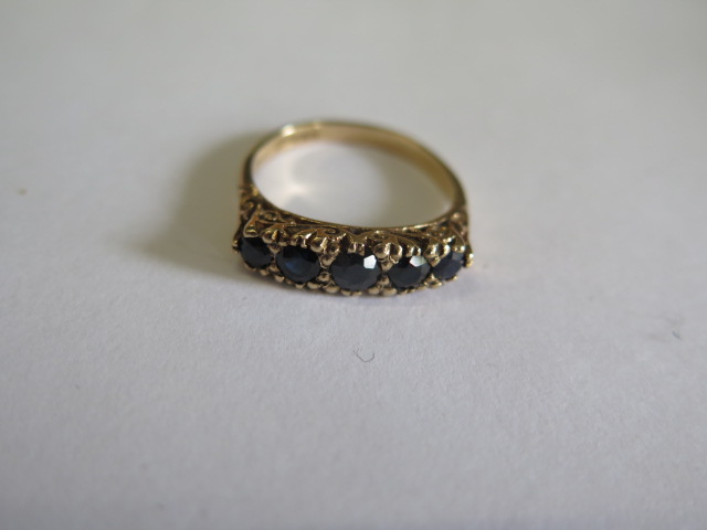 A hallmarked 9ct yellow gold five stone ring, possibly dark sapphires, size O, in good condition