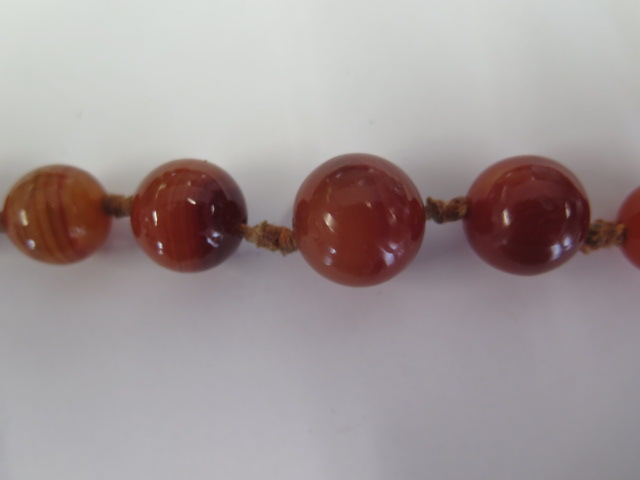 An agate necklace, 64cm long, largest bead approx 15mm, generally good condition, some wear to - Image 2 of 2