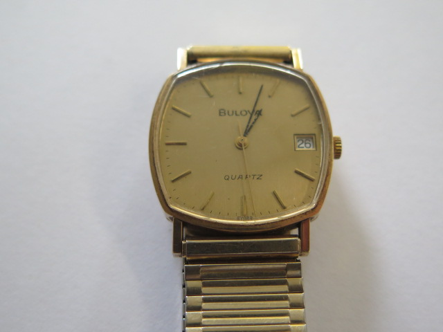 A hallmarked 9ct yellow gold Bulova quartz date wristwatch, 30mm wide on a plated strap, in - Image 2 of 4