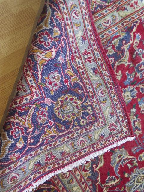 A rich red ground hand woven woollen full pile Persian Kashan carpet with traditional floral - Image 8 of 8