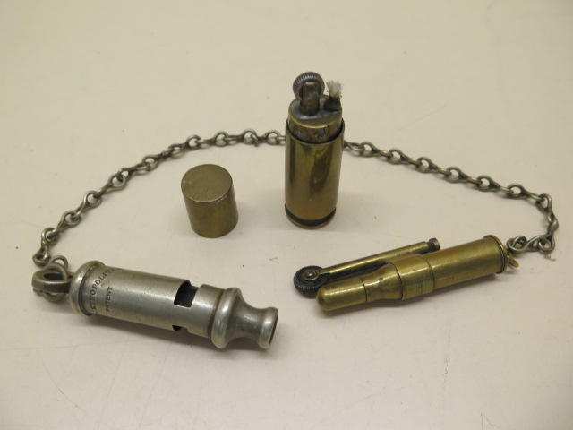 Two trench lighters and a dented Metropolitan whistle