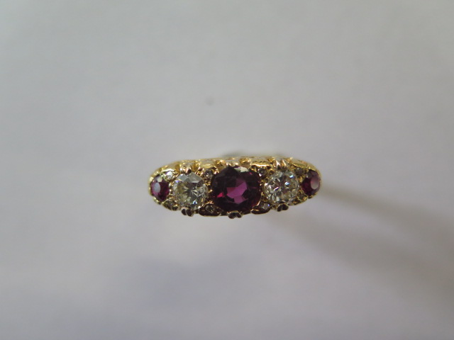 A ruby and diamond modern 'boat' ring in yellow colour metal, graduated size stones comprising of