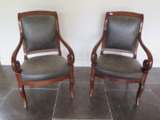 A pair of 19th French mahogany fauteuils scroll arm open armchairs with reupholstered leather