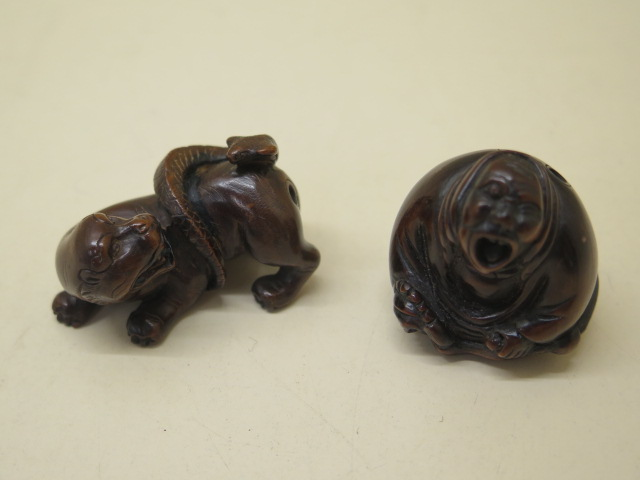 Two carved wooden Netsukes of a lion and serpent, 4.5cm tall and a seated figure 3.5cm tall, both